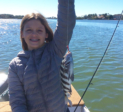 Girl holding her catch out in the Sarasota Intercoastal Waterway