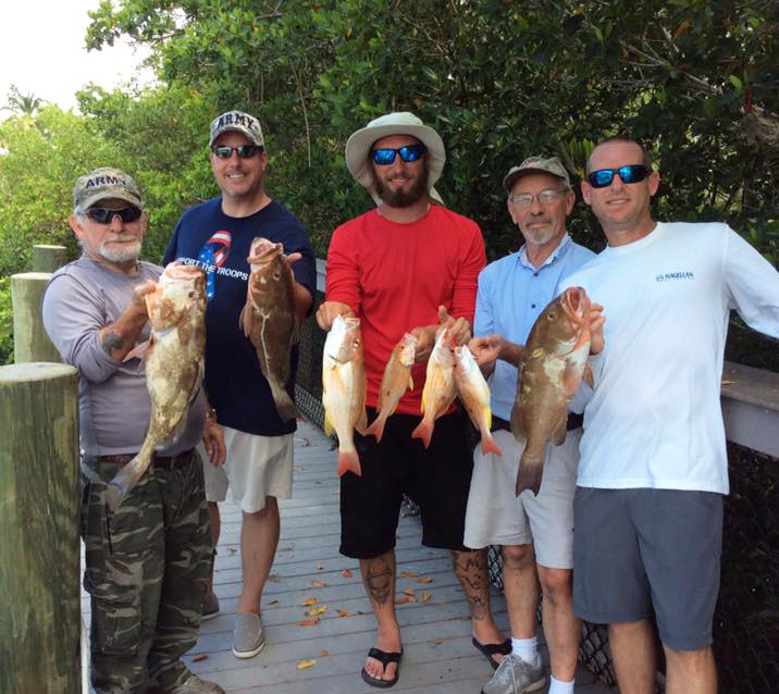 group of guys holding their grouper